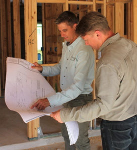 two designers reviewing plans on job site