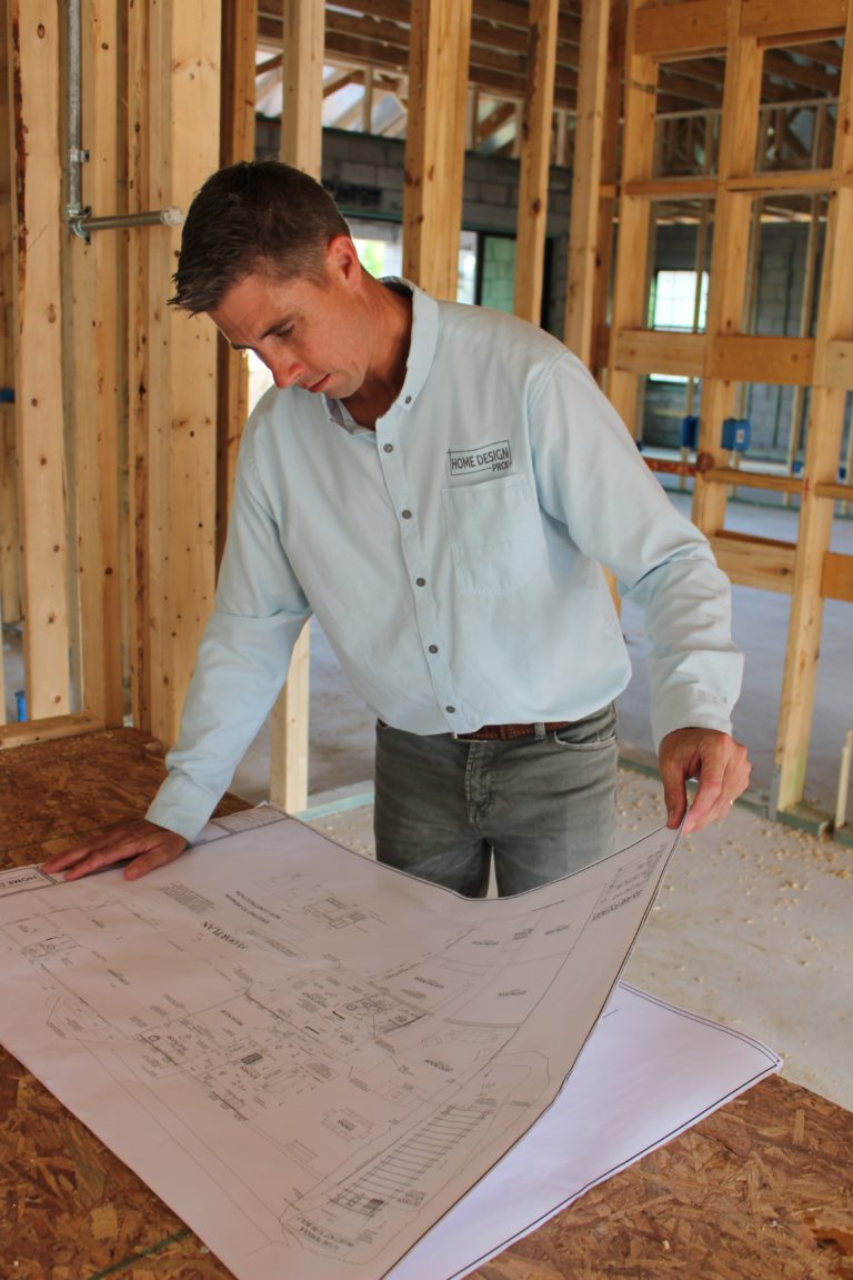 Residential designer reviewing plans on construction job site